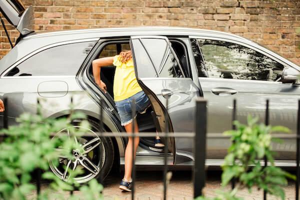 A girl climbing into a car